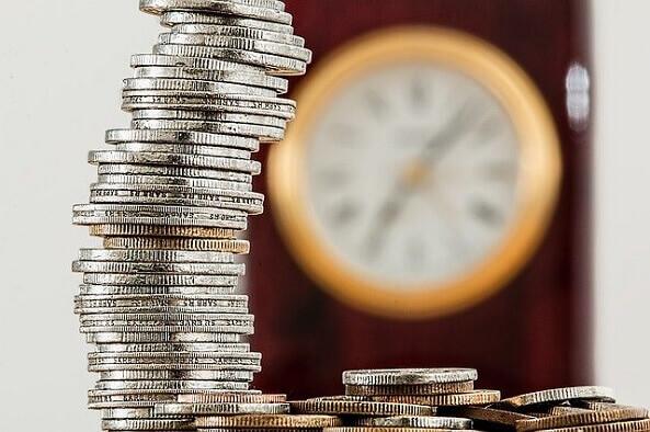 stos monet, w tle zegar