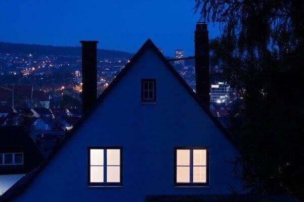 grafika przedstawiająca wieczorny widok na miasto, w pierwszym planie dom jednorodzinny z zapalonymi światłami