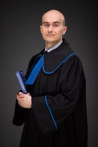 zdjęcie radcy prawnego dr Radka Rafała Wasilewskiego w todze radcy prawnego z książką prawniczą